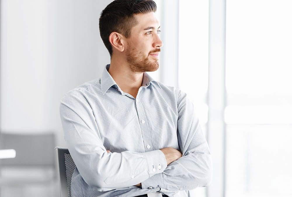 Young Caucasian man looking outside window with arms crossed